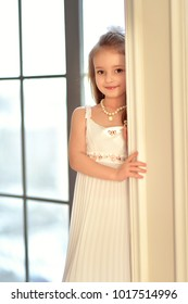 Young girl in white dress near portiere on window background