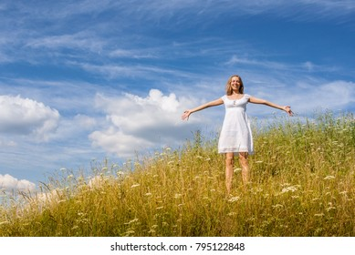Young girl in white dress is standing on grass hill with outstretched to sides hands on blue cloudy sky background in summer day.