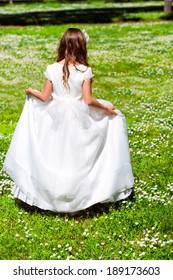 Young girl in white dress walking in flower field.