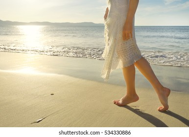 Young girl in white dress walking alone on the sandy tropical beach at sunrise.Closeup detail of female feet and golden sand on beach.