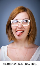 young girl in white glasses in a good mood with his tongue hanging out