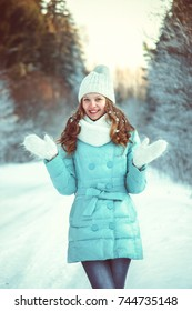 a young girl with white hair, like a doll, in a knitted scarf and mittens, a blue down jacket, in a winter snowy forest - a park. She scattered snow on her hair and laughs.