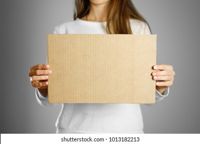 A young girl in a white jacket holding a piece of cardboard. Prepared for your text.