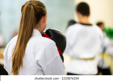 Young Girl In White Karate Gi with Boxing Gloves Standing in Class