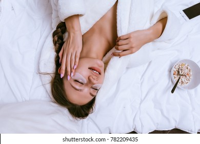 young girl in a white robe lies on the bed, early in the morning, under the eyes patches