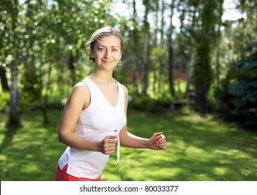 Young girl in a white shirt and red pants likes to run outdoors.