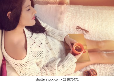 Young girl in a white sweater drinking tea with lemon