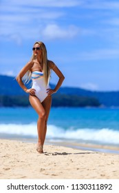 Young girl in white swimsuit posing at Karon beach, Phuket, Thailand