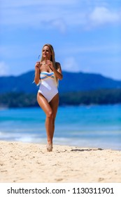 Young girl in white swimsuit walking at Karon beach, Phuket, Thailand
