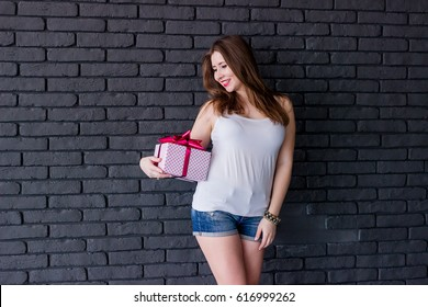 A young girl in a white T-shirt and jeans shorts stands on a gray brick wall and holds a gift with a bow