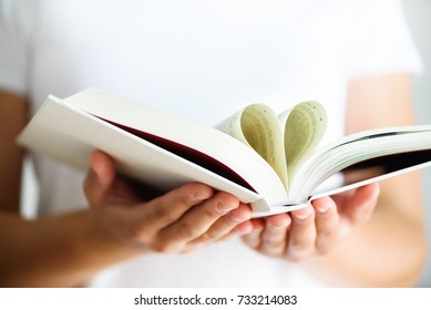 Young girl in white T-shirt reading opened book with shape of heart, love concept. Copy space.