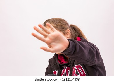 Young girl who denies being photographed shielding her face with hand in foreground