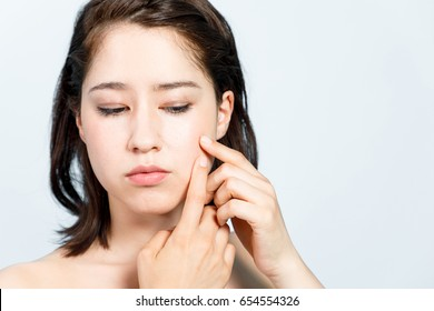 young girl who popping her pimple. skin care concept. acne treatment.