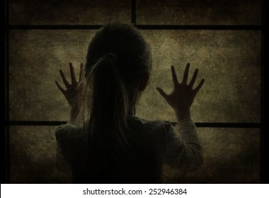 Young girl at window (in dark silhouette) hands pressed against window, pensive or wanting out?