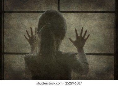 Young girl at window (in silhouette) hands pressed against window, pensive or wanting out?