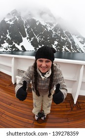 Young girl in winter clothes on the ship in Antarctica shows that all is well. Photo taken fish-eye lens