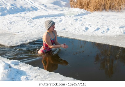 young girl in winter swims in a lake, extreme swimming