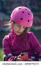Young girl wit skateboard helmet looking at smartphone.