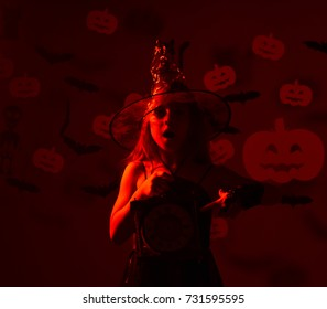 Young girl in witch halloween costume with big old clock and scared face over dark red background. Halloween time concept