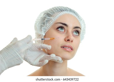 young girl without makeup in the medical Cap raised her eyes up and cosmetologist makes her prick at face close-up