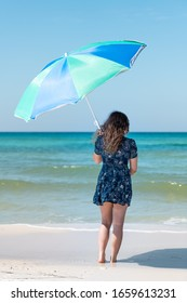 Young girl woman back standing on beach on sunny day with hair in wind in Florida panhandle with ocean on gulf coast