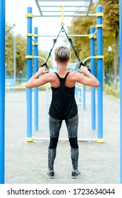 young girl, woman doing exercises outdoors using slings, TRX loop