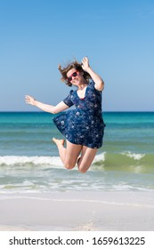 Young girl woman happy jumping mid-air on beach on sunny day with red sunglasses in Florida panhandle with ocean on gulf coast