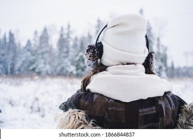 Young girl, woman in knitted mittens listening to music on headphones. Walking in beautiful winter forest among trees, firs, covered with snow. Magnificent nature. Fashionable image,clothes,parka,hat.