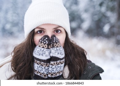 Young girl, woman in knitted mittens feels cold. Walking in beautiful winter forest among trees, firs, covered with snow. Magnificent nature. Fashionable image, clothes, parka, hat, blue jeans.