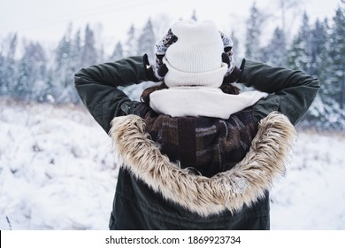 Young girl, woman in knitted mittens lost in forest woman holding her head.Walking in beautiful winter forest among trees,firs,covered with snow.Magnificent nature.Fashionable image,clothes,parka,hat.