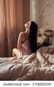Young girl woman with long dark hair in a light nightdress sits with her back in a large bed in a beige bedroom