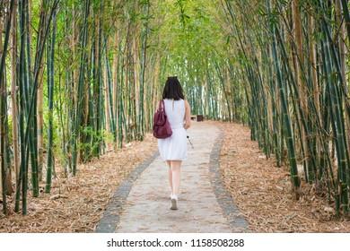 Young girl woman walking away in a  bamboo path.