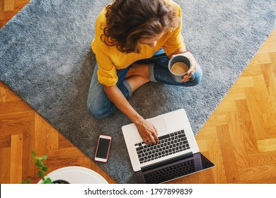young girl woman in a yellow shirt works on a laptop with a mug of coffee at home in the living room on the carpet, remote work and education
