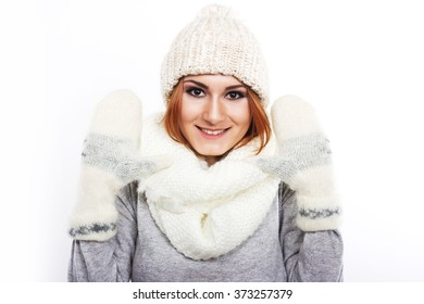 Young girl in a woolen hat and scarf. A girl dressed warmly. Winter cold. Portrait of a girl with big eyes on a white background