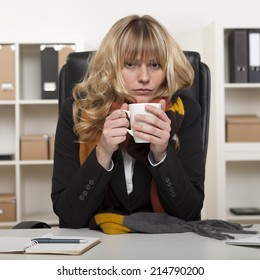 Young girl at work sitting at her desk in the office with a warm winter scarf around her neck enjoying a mug of hot coffee