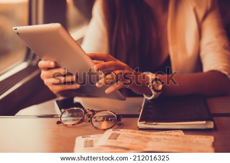 Young girl works on the tablet on the internet and goes to the train, ipad surfing, woman using smartphone, holding tablet in hand, send answer texts, travel in train, office manager, hipster