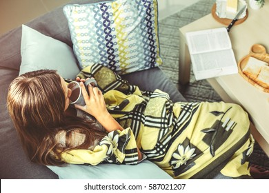 Young girl wrapped in blanket relaxing on a couch in living room. Comfortable weekend morning, top view.