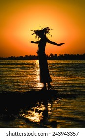 Young girl in a wreath dancing at sunrise (sunset) on the banks of the river.