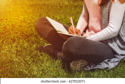 Young girl writes with pen in notebook sitting on green grass in park on meadow. Education and recreation