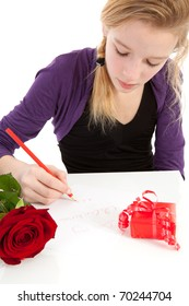 Young girl is writing Be my valentine in closeup with rose and present
