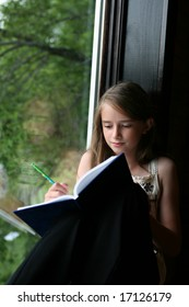 young girl writing in her journal while sitting at a large window