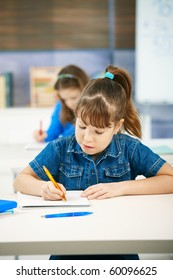 Young girl writing at school sitting in class with other girl in background.?