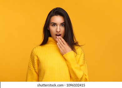 Young girl in yellow sweater covering mouth with hand looking astonishment on orange background.