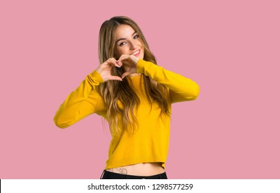 young girl with yellow sweater making heart symbol by hands on isolated pink background