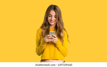 young girl with yellow sweater sending a message with the mobile on isolated yellow background