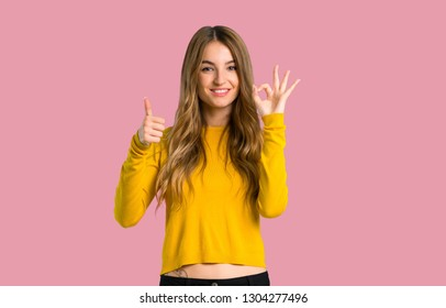 young girl with yellow sweater showing ok sign with and giving a thumb up gesture on isolated pink background
