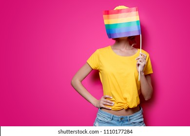 Young girl in yellow t-shirt and blue jeans holding big LGBT flag on pink background