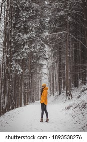 Young girl in yellow winter jacket and with an uncomprehending smile looks at her partner. Woman aged 20-24 is standing in the middle of snowy road and it is snowing around her. Set Sail Champagne.
