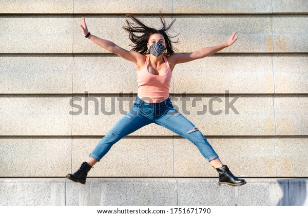 young girl of the Z generation wearing a leopard mask does an acrobatic jump with open legs, concept of positive thinking and optimism, motion trail effect on feet