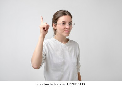 Young girlfriend has idea to solve problem. Portrait of clever attractive european female raising index finger.